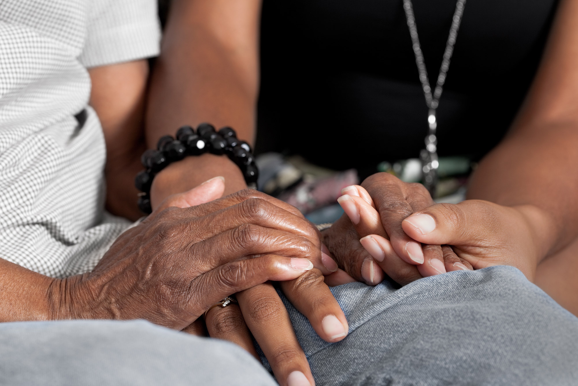 A photo of two people holding hands in a comforting way