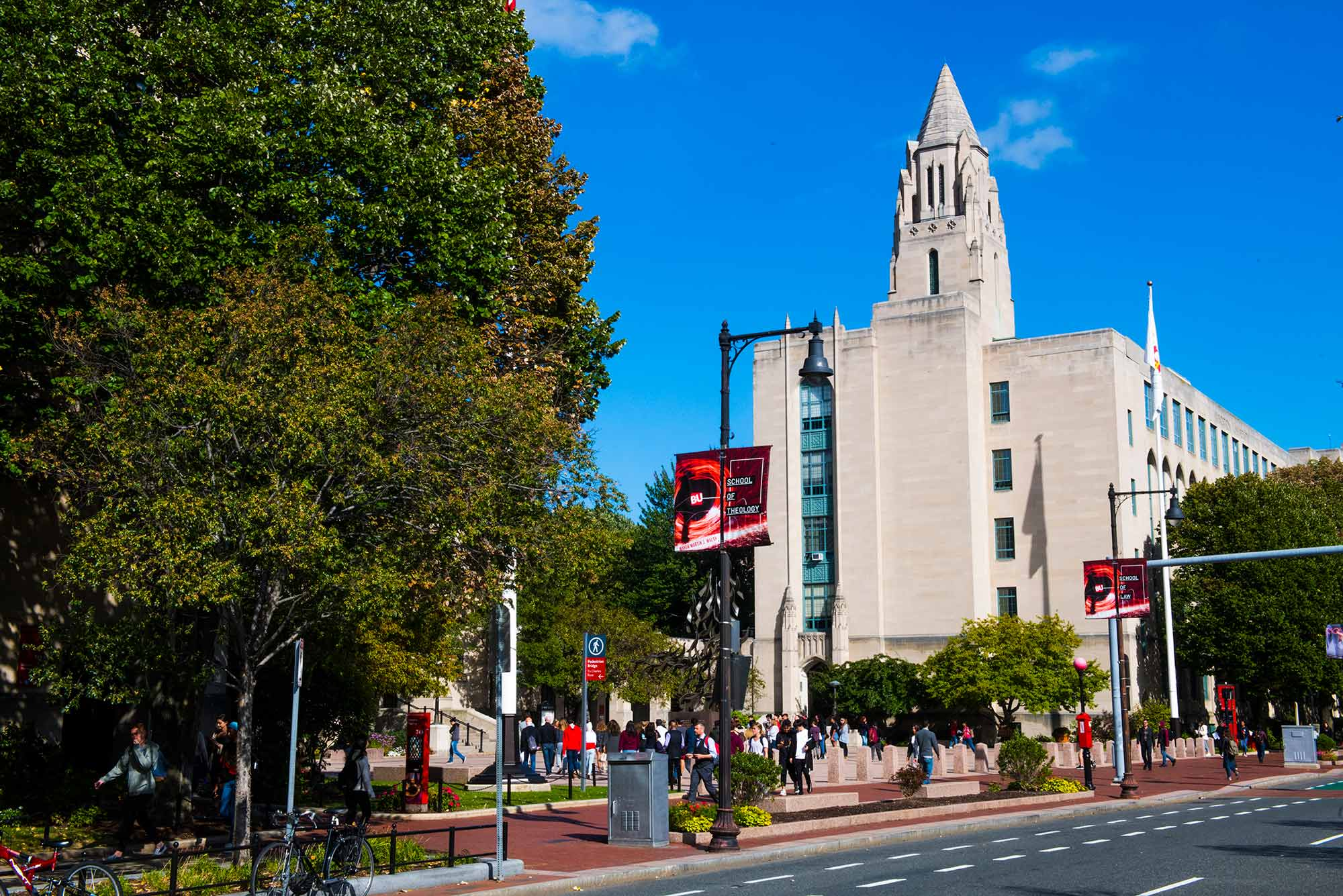 Photograph of Marsh Plaza from across the street with CAS building in background. The plaza is busy with people.Red banners seen throughout image. It's a sunny day at the start of the fall semester.