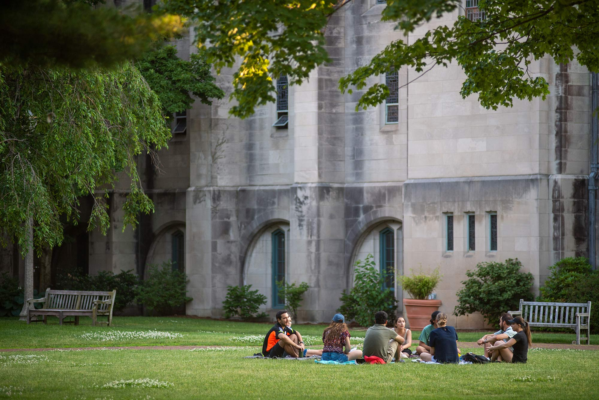 A group of students sit on blankets in the grass behind Marsh Chapel, a tree is seen in the top left of the photo.