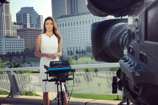 Photo of Kristin Fisher behind a light and a camera in a white dress reporting with a city skyline behind her.