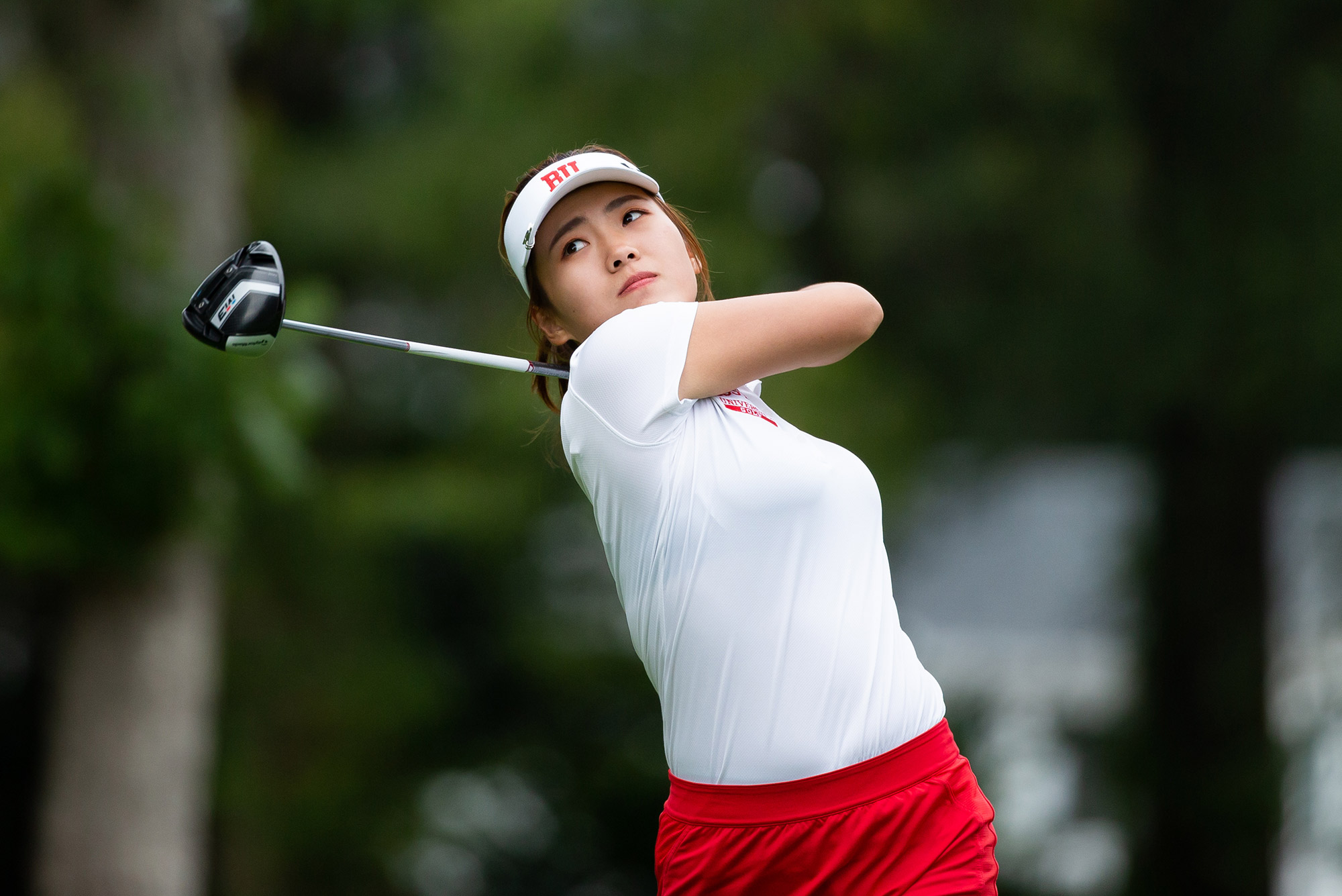 "Women's golf team member Zhangcheng ""Kristy"" Guo at the end of her golf swing. She wears a white shirt and hat."