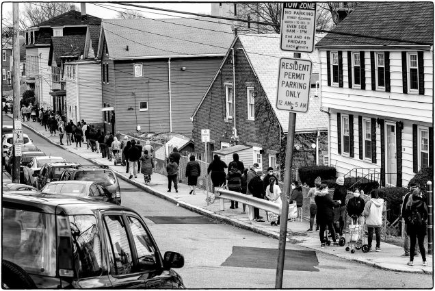 "Photo of a group of Chelsea, Mass. residents lined up, many in sweatshirts or jackets, to pick up food at a food pantry. The photo shows a long line on the other side of the street, with a car and a ""Resident Parking Only"" Sign in the foreground. The photo is black and white."