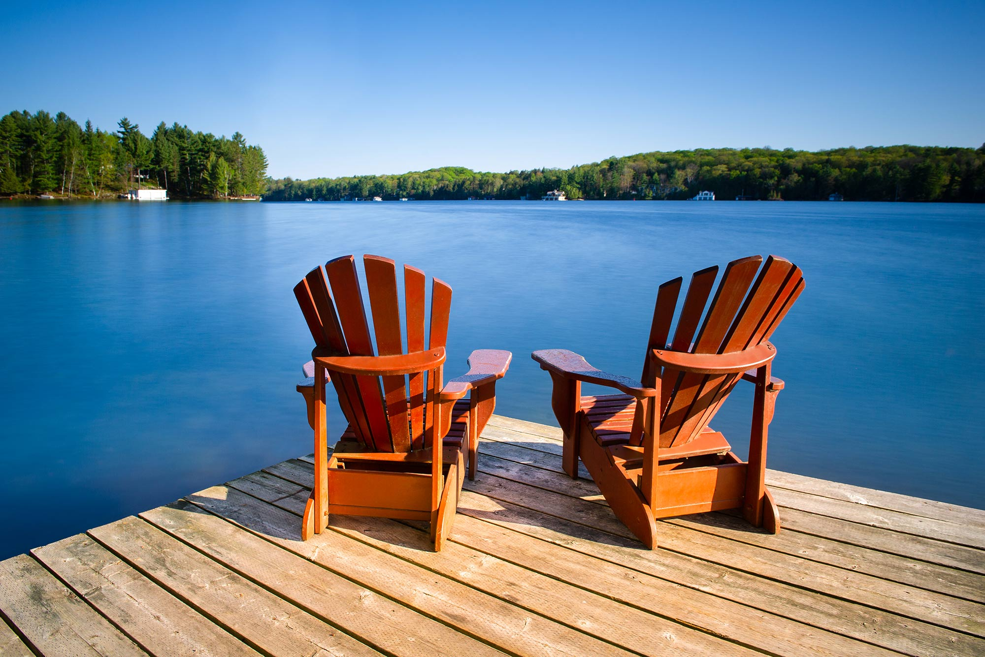 Photo of Adirondack chairs on a wooden dock on a calm lake in Muskoka, Ontario Canada. Cottages nestled between trees are visible across the water.