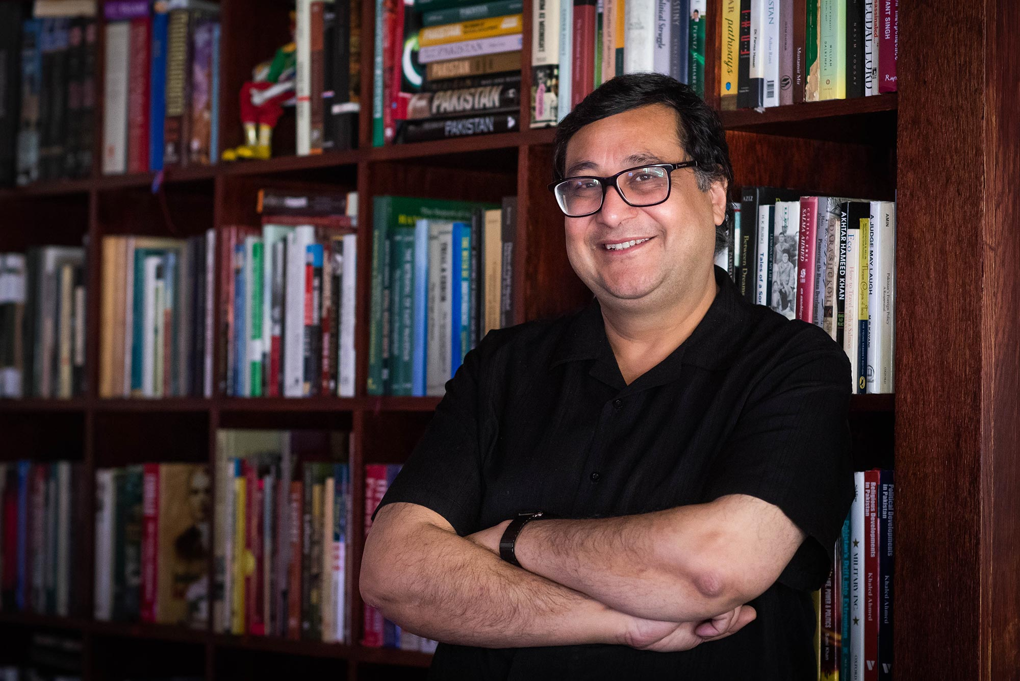 A photo of Adil Najam standing in front of a bookcase in his home with his arms crossed in front of himself