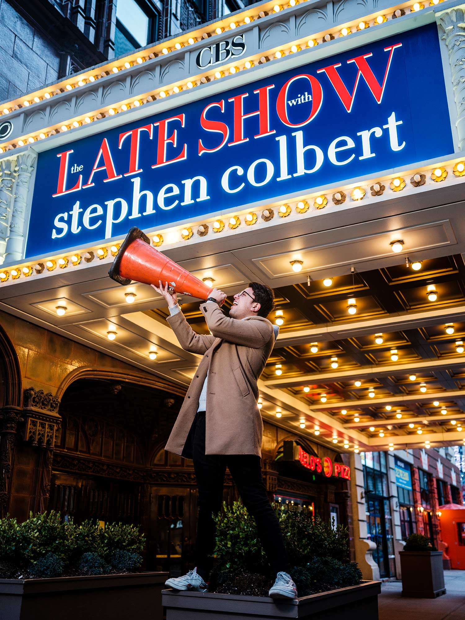 Felipe Torres Medina, a staff writer for The Late Show with Stephen Colbert, poses outside of the Late Show sign and yells into an orange traffic cone as if it were a megaphone.