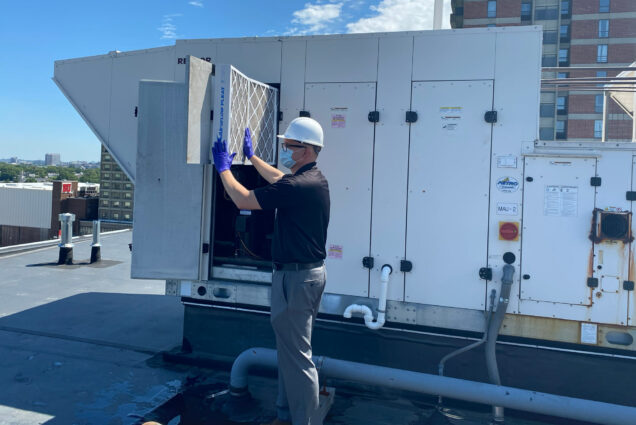 Elijah Ercolino, director of the Facilties Engineering Group, inspects an HVAC air filter on the roof of 1047 Commonwealth Ave.