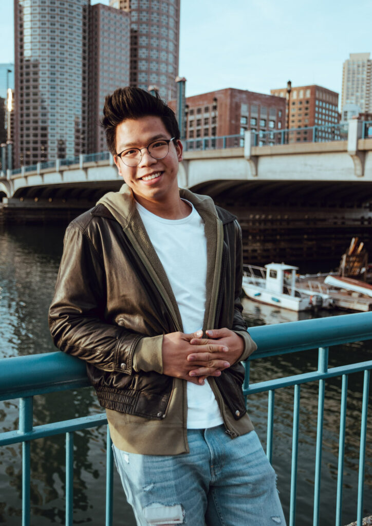 A photo of Zhou standing on a bridge leaning against the railing and smiling at the camera