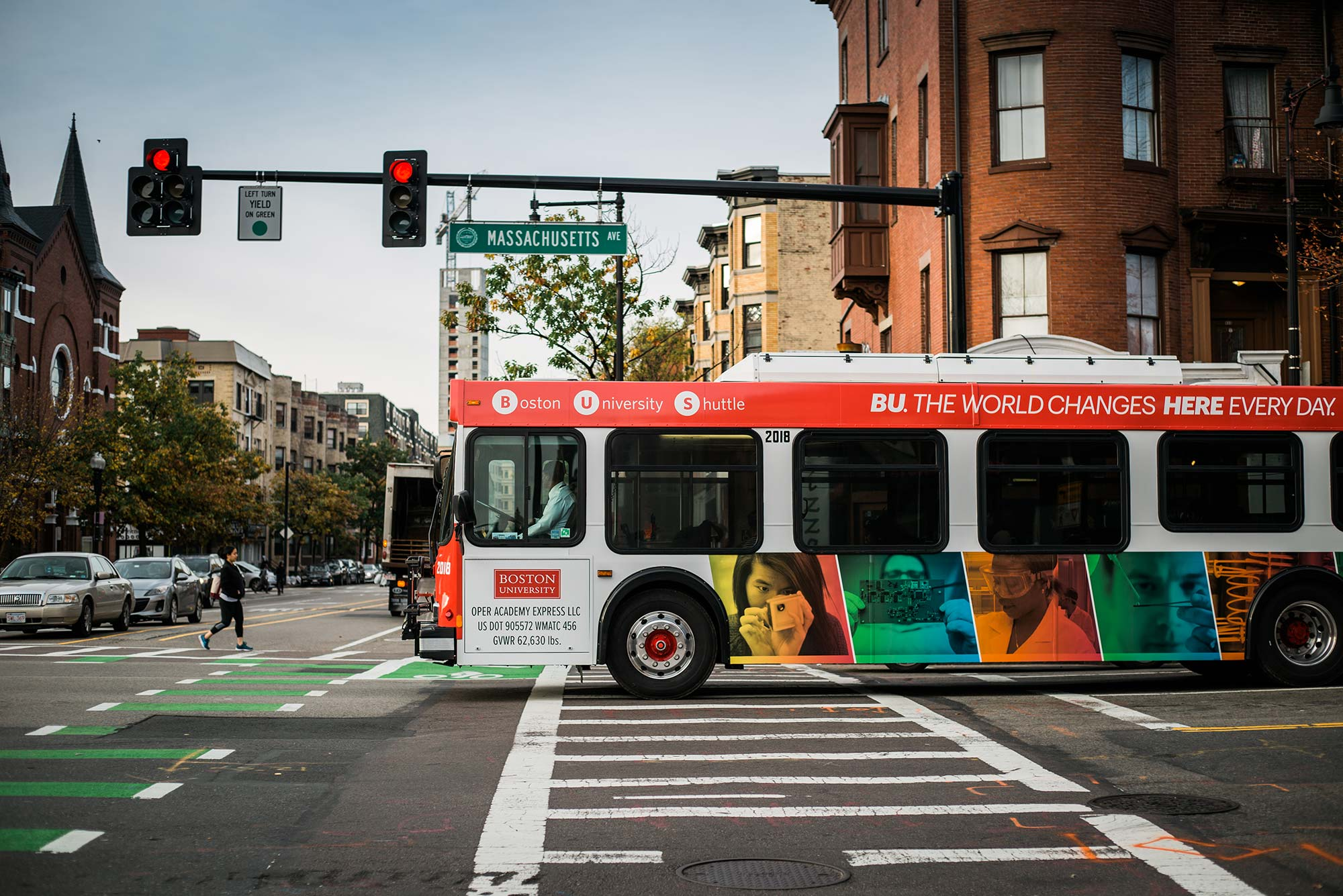 Photo of a BU shuttle driving through an intersection along Mass Ave. The bus has colorful photos on it and a cross walk is seen on the pavement. A pedestrian is seen crossing the street in the distance.