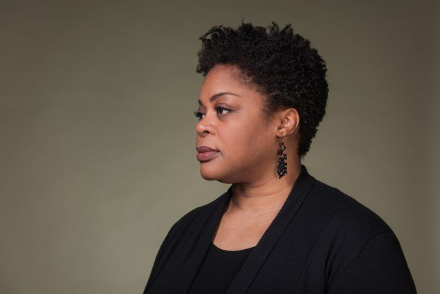 Portrait of Crystal Williams, a College of Arts & Sciences professor of English, who leads BU efforts on diversity and inclusion who has been recently promoted to Vice President and Associate Provost of Community and Inclusion. In the portrait, Williams wears a black blouse and earrings, and looks off into the distance on a dark green backdrop.
