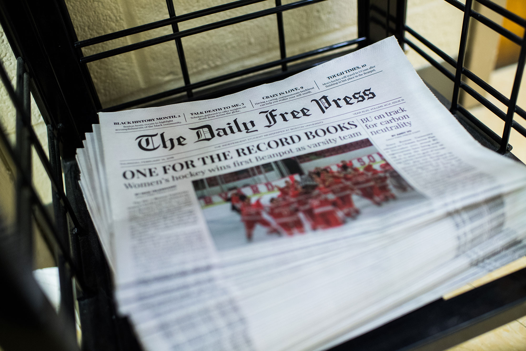 "Photo of a stack of The Daily Free Press newspapers stacked in COM building on Friday, February 15, 2019. The headline reads ""One for the Record Books"" and has an image of BU Hockey team celebrating."