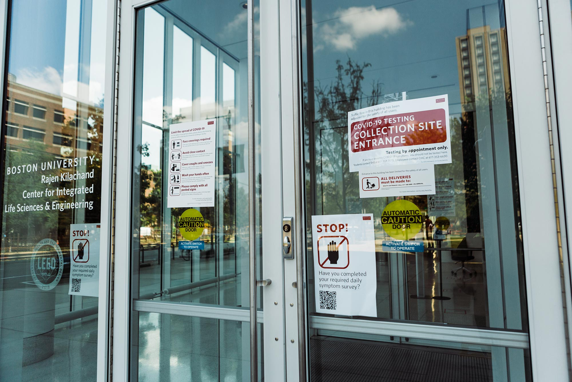 "Photo of the glass door at the entrance of the Rajen Kilachand Center at Boston Univeristy. Paper signs on the door read ""COVID-19 Testing Collection Site Entrance"" and ""Stop! Have you completed your required daily symptom survey?"""