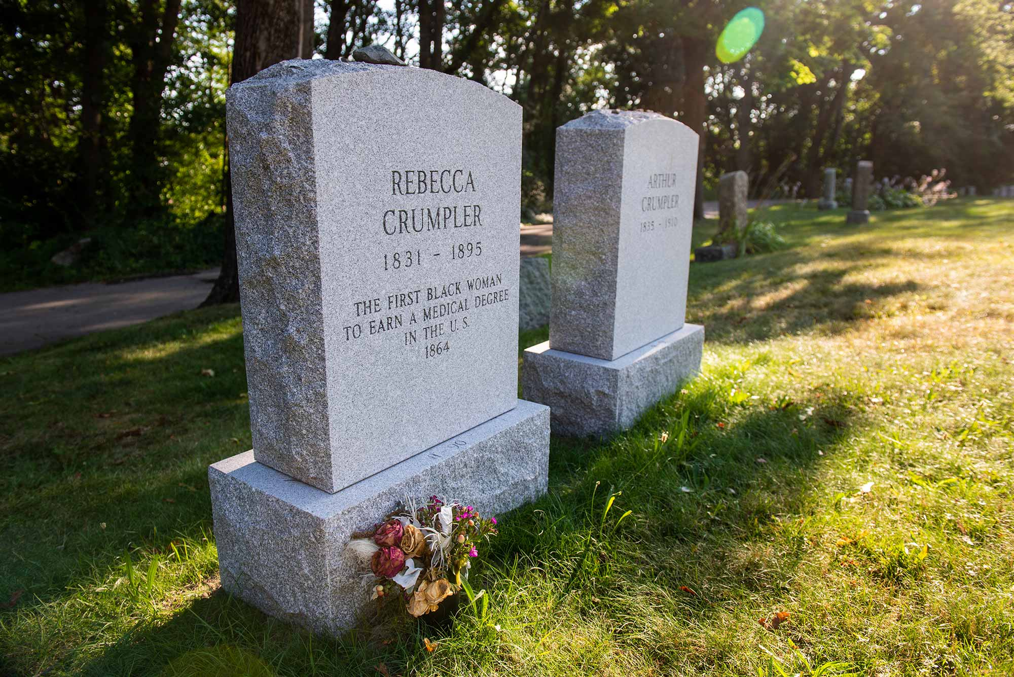 "Photo of the headstones of Rebecca Lee Crumpler (MED'1864), reading ""the first Black woman to earn a medical degree in the US."" and her husband Arthuer Crumpler. The headstones are at the Fairview Cemetery in Hyde Park. Bright green grass grows around the headstones."