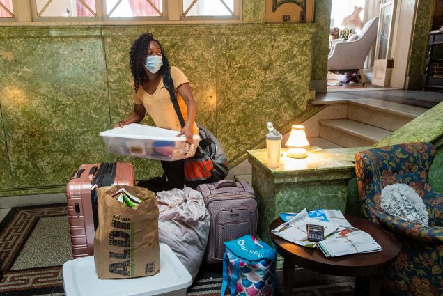 Photo of the lobby of the Harriet E Richards Cooperative (HER) House on Bay State Rd in which Tiana Catala (COM'22) collects her things to move into to her room at HER House. She wears a blue medical mask and is seen lifting a plastic tub of her belongings.