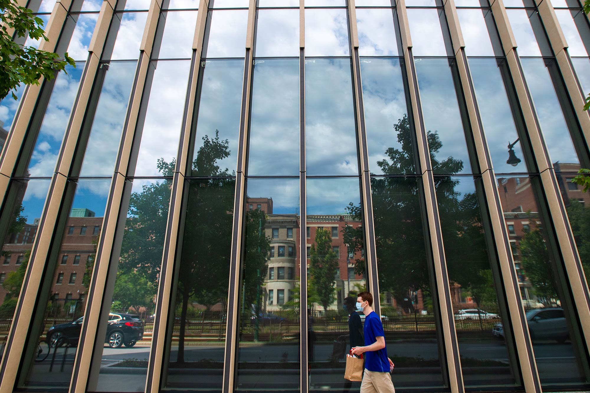 Photo of cloudy blue skies reflect in the windows at CILSE where COVID testing is also being made available to members of the BU community August 19. A student in a mask holds a bagged lunched and walks by.
