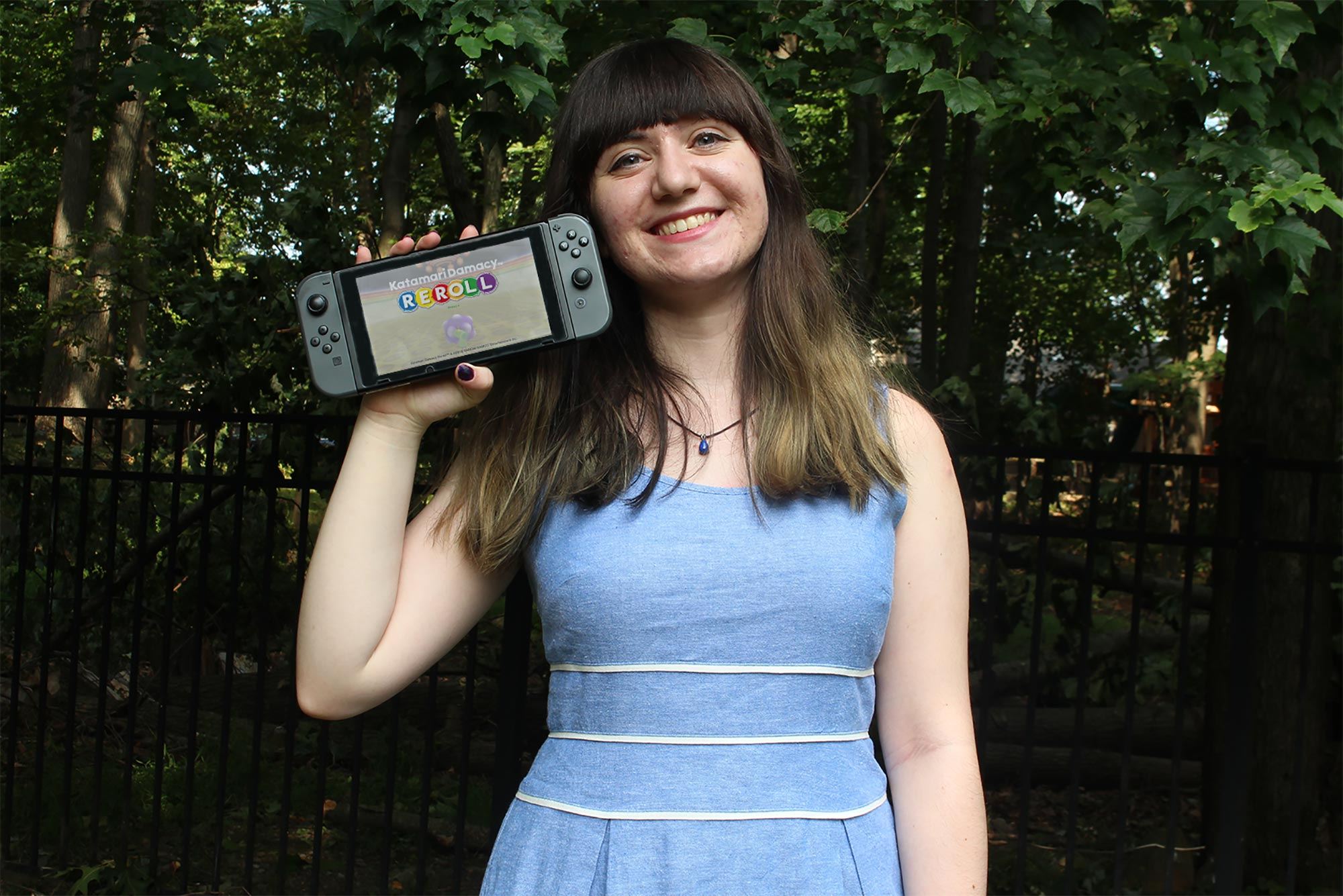 Photo of Sabrina Scotti (CFA'20) in a light blue dress holding Katamari Damacy REROLL, one of the children's video games she studied as part of her an Undergraduate Research Opportunity Program–funded research into whether games use diverse music styles to further music education. She smiles and bushes are seen in the background.