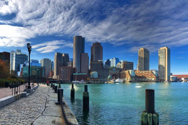 Photo taken from Boston Seaport looking towards the Boston skyline. The water is light blue, and the sky is blue with some clouds.