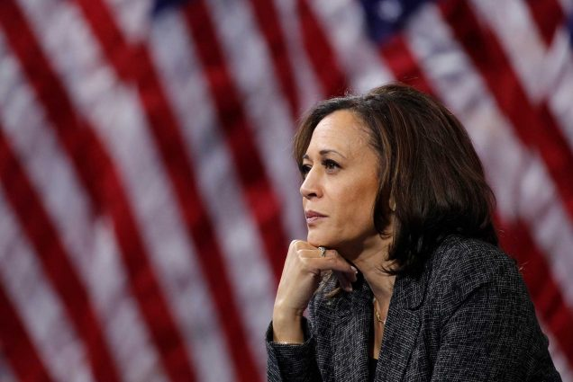 California Senator Kamala Harris sitting in front of United States flags with her chin resting on her hand.