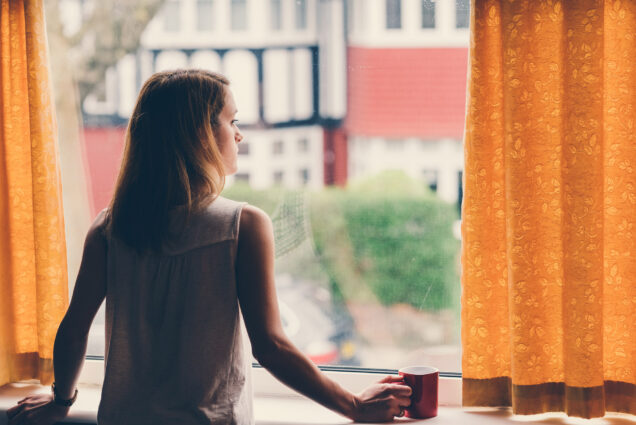 A photo of a woman holding a coffee mug staring out of a window
