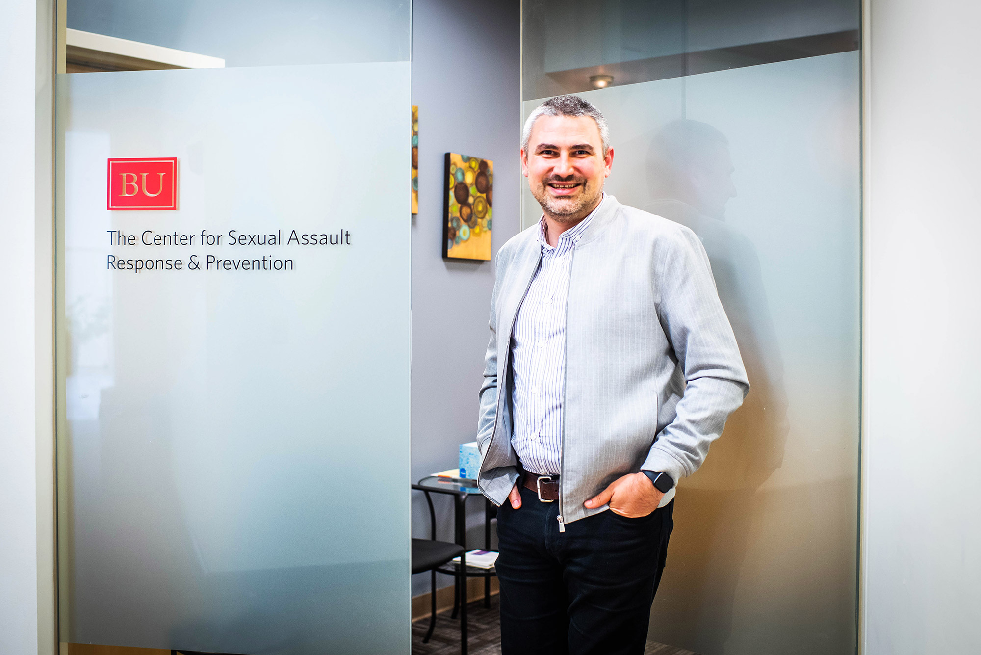 "A photo of Nathan Brewer standing in front of a sign that reads ""Center For BU Sexual Assault Response & Prevention"""
