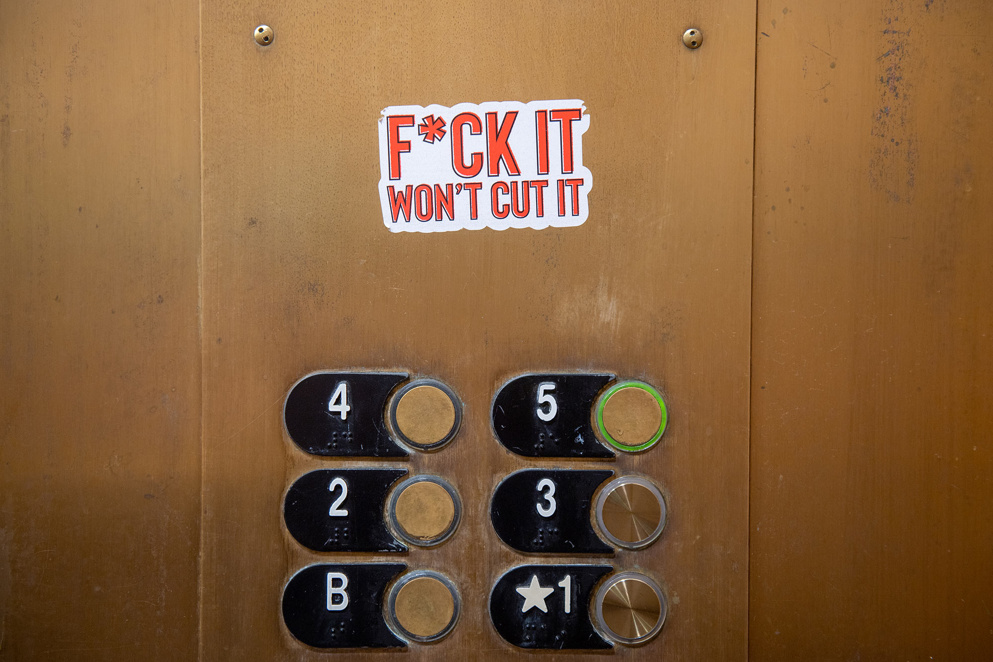Photo of a f*ck it won't cut it sticker inside a CAS elevator on September 13. The buttons of elevator are seen below.