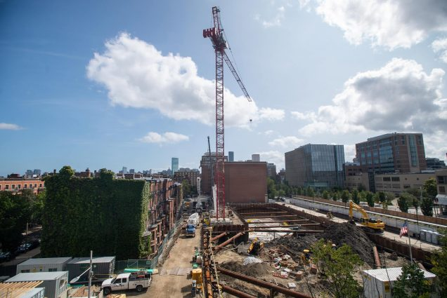Photo of continued construction at Data Services Center, including the addition of a massive red crane that cuts in the city skyline. Work trucks and metal beams are seen around the construction site.