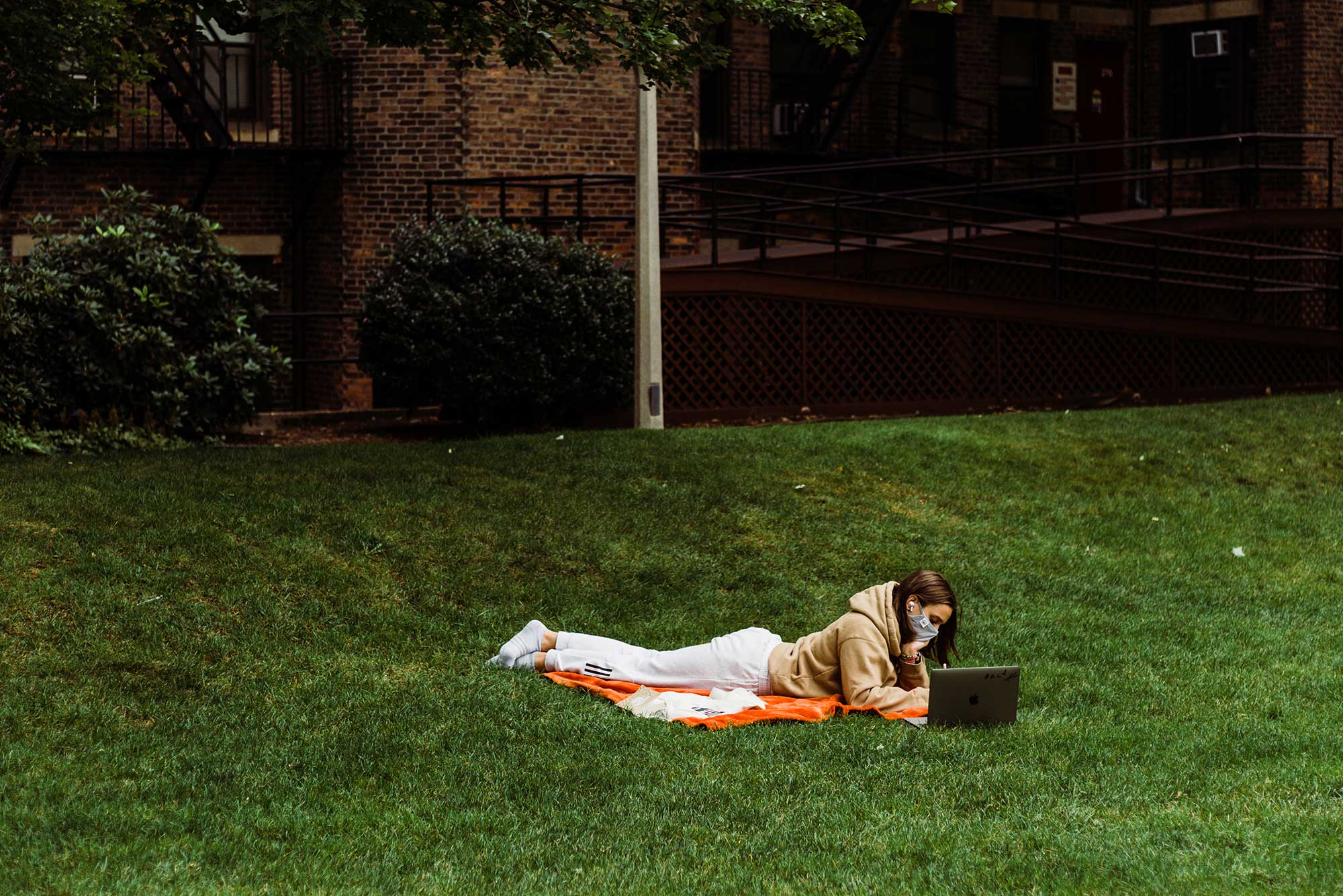 Photo of a student in a sweatshirt laying down in the grass at BU Beach in a mask. The student works on their laptop.