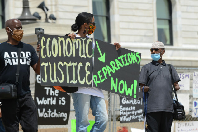 "Photo of Juneteenth reparations rally to demand reparations from the United States government. A rally-goer holds two signs, one says ""economic justice"" while the other says ""reparations now!"" Other masked individuals are seen in the frame."