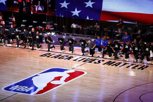 "Photo of Players from Orlando Magic and Milwaukee Bucks who took a knee during the national anthem before the start of Game 3 of an NBA basketball first-round playoff series, Saturday, Aug. 22, 2020, in Lake Buena Vista, Fla. The players where black lives matter t-shirts. The court parquet floor reads ""Black Lives Matter"" and has a large NBA logo. The American flag is seen behind the kneeling players."