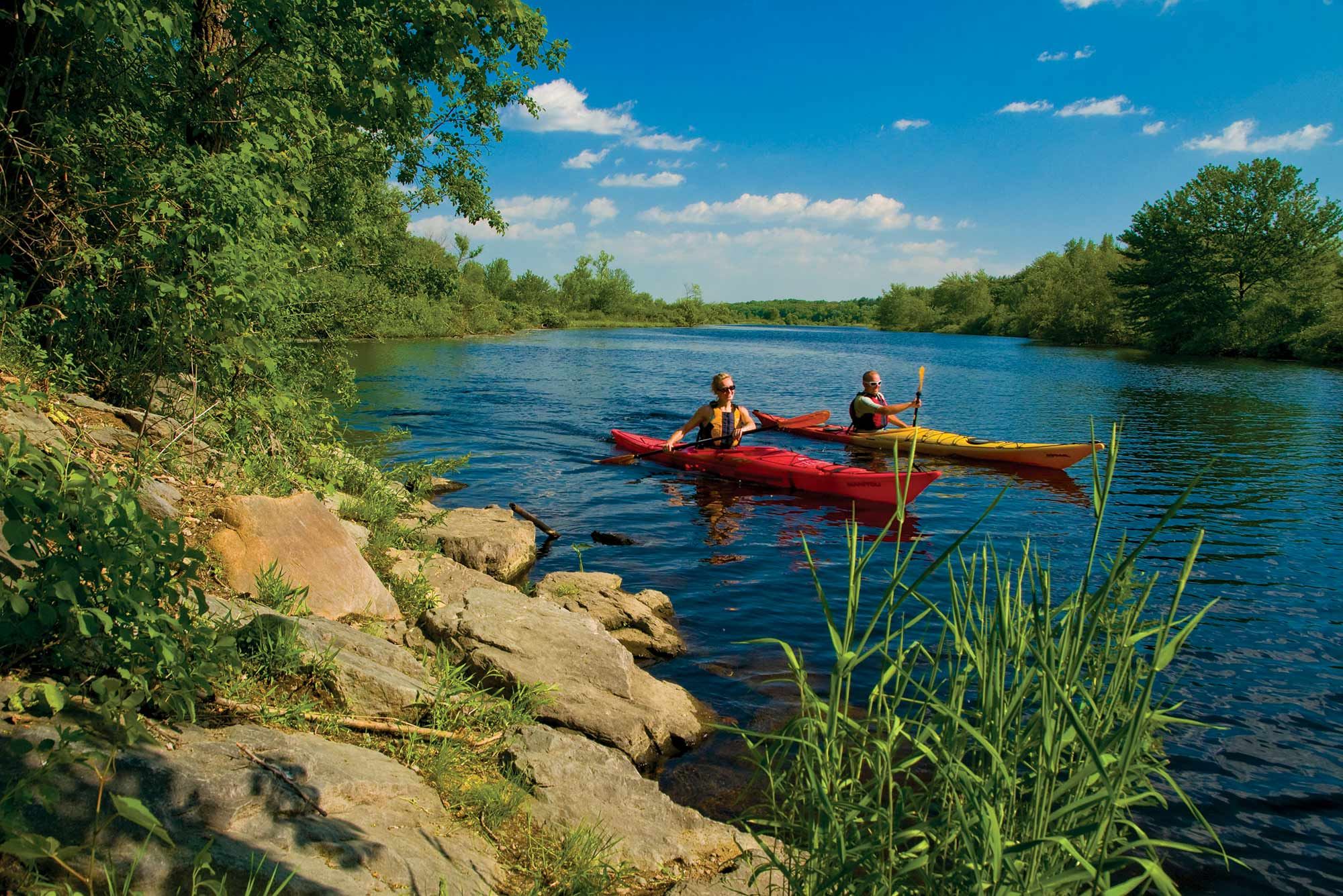 Image of two people kayaking on a river on a sunny day. One kayak is red, the other yellow. Photo taken from the shoreline, rocks and brush are seen in the foreground.
