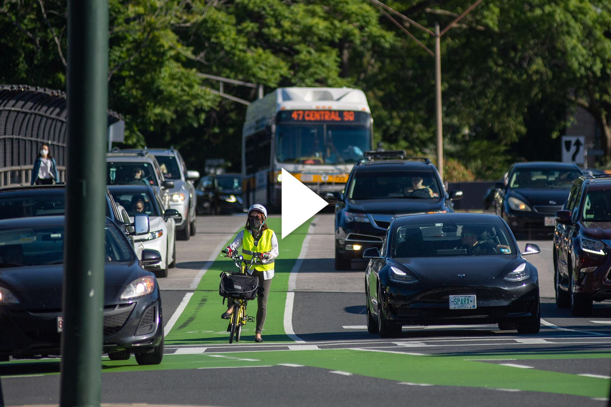 Photo of a person in a green vest and helmet on a bike waiting in a bike lane at a light. Many cars and city buses are seen around them. Overlay has video play button.