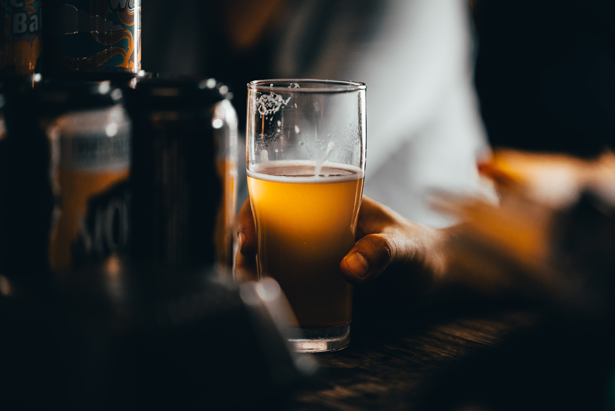 Photo of a hand holding beer; the beer and glass are in the light, while the background is blurry but resembles a bar.