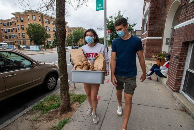 Photo of Flagg (left) and her boyfriend, Aaron Bourget, picking up a donation from Bagelsaurus in Cambridge during a volunteer shift for Rescuing Leftover Cuisine in August. Both wear masks, Lizy carries a tub with brown bags.