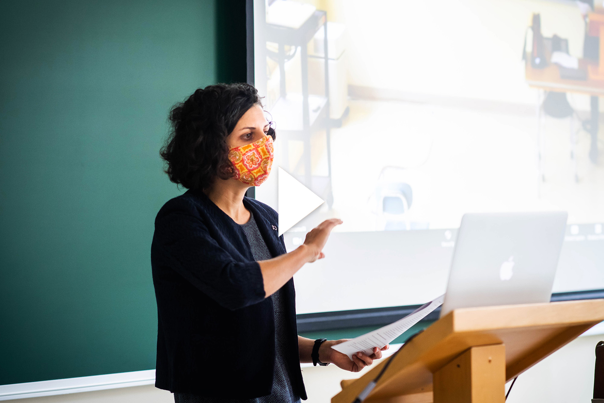 "Photo of Caterina Scaramelli teaching an anthropology class, ""Culture & Environment "" on September 22, 2020. She wears a bright orange mask as she lectures to her computer and the students in the class. Overlay has video play button."
