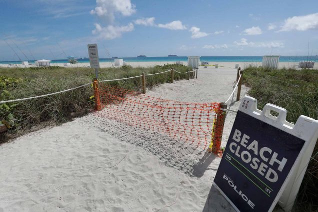 A Beach Closed sign stands at the entrance to Miami, Florida's famed South Beach, March 2020.