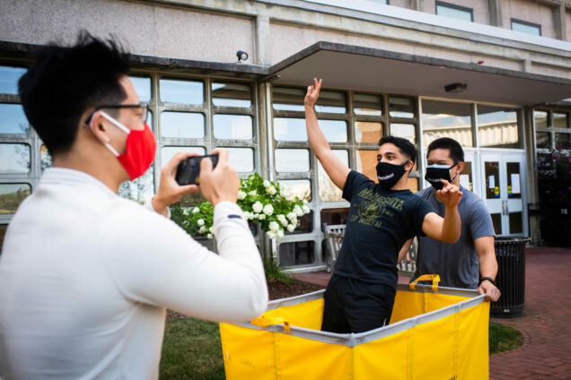 RAs Dragon Ding (CAS'21) (from left) records a video of John Issac (CAS' 21) and Lance De Guzman (Sargent'22) on August 17. Issac stands in a yellow moving cart and De Guzman