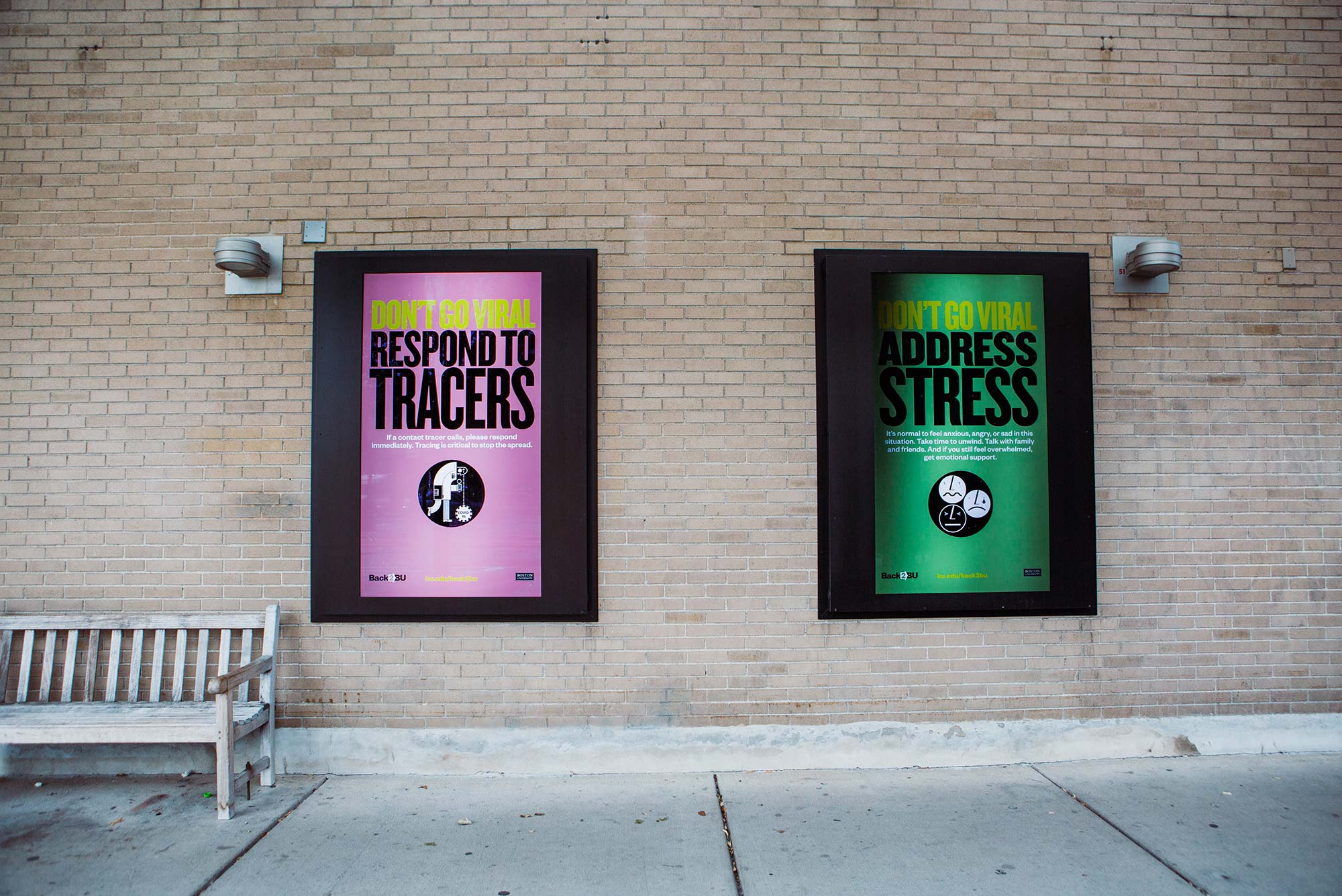 "Photo of two signs outside of warren towers. The one on the right is purple and says ""Don't go Viral, respond to tracers."" The right one is green and says ""Don't go viral, address stress"""