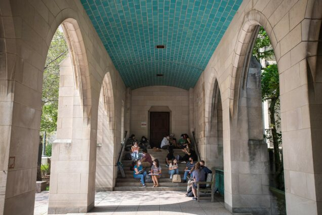 Photo of political science lecturer Rachel Meade's class taking place in the overhang next to Marsh Chapel September 14. Students sit on the steps inside the overhang and sunlight shines through the arches.