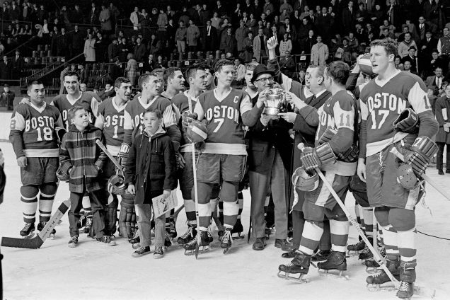 Black and white photo of men's hockey team on the ice after Boston University defeats Northeastern 4-0 in the Beanpot Tournament final game. BU Players include Herb Wakabayashi #18, Jim Quinn #7, Pete McLachlan #11, Bill Hinch #17. David Kelley on ice with his dad, Coach Jack Kelley.