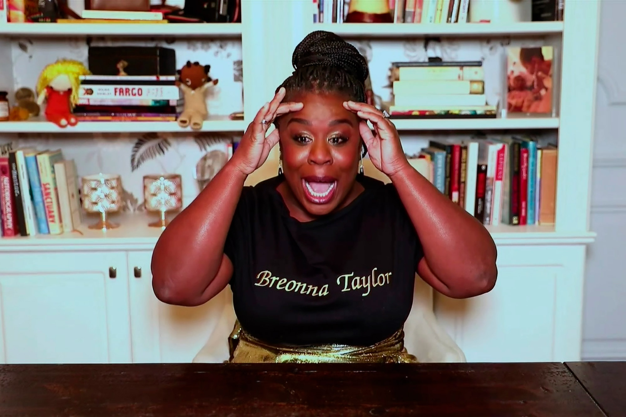 "Photo of Uzo Aduba wearing a black t-shirt that says ""Breonna Taylor"" on it in gold, as she remotely accepts the Emmy for Outstanding Supporting Actress in a Limited Series or Movie for ""Mrs. America"" during the 72nd Emmy Awards telecast on Sunday, Sept. 20, 2020."