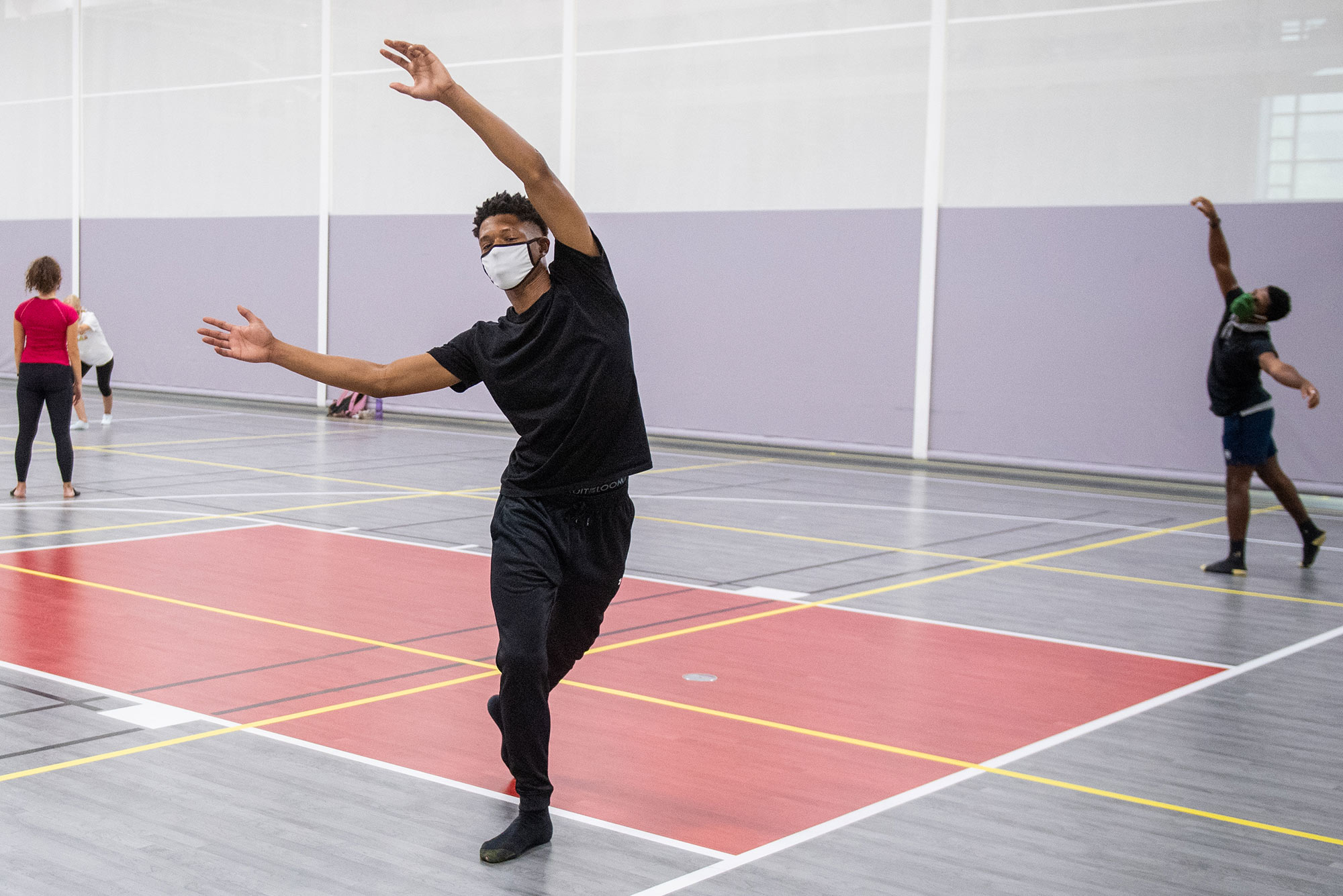Photo of Bishop Edwards (CFA'23) moving within his 14-foot square during instructor Liz Roncka's improv dance class at FitRec September 3. The yellow tape grid is there to ensure physical distancing. Bishop raises both his hands in the air gracefully and wears a blue mask.