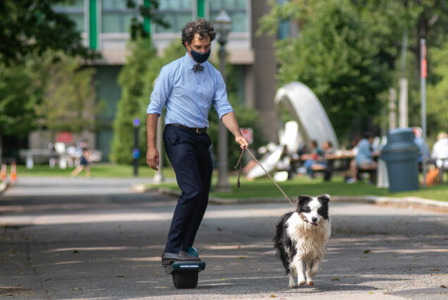 Photo of Professor of earth and environment Bruce Anderson heading back to his office on an electric hoverboard after getting some fresh air with his 1.5 year old pup Juke, a shaggy back and white dog that runs by his side as Anderson holds its leash.