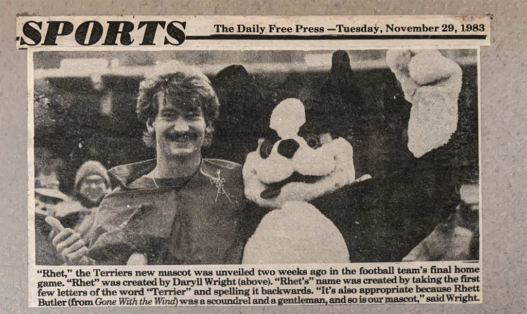"Photo of a newspaper clipping sjpwomg Braden Wright (COM'86), who named ""Rhet,"" with the mascot at a football game in 1983, before the the second T was added. A headline reads ""Sports: The Daily Free Press—Tuesday Tuesday, November 29, 1983."" Caption below reads ""Rhet,"" the Terriers new mascot was unveiled two weeks ago in the football team's final home game. ""Rhet"" was created by Daryll Wright (above). ""Rhet's name was created by taking the first few letters of the word 'terrier' and spelling it backwards. ""It's also appropriate because Rhett Butler (from Gone with the Wind) was a scoundrel and a gentleman, and so is our mascot,"" said Wright."