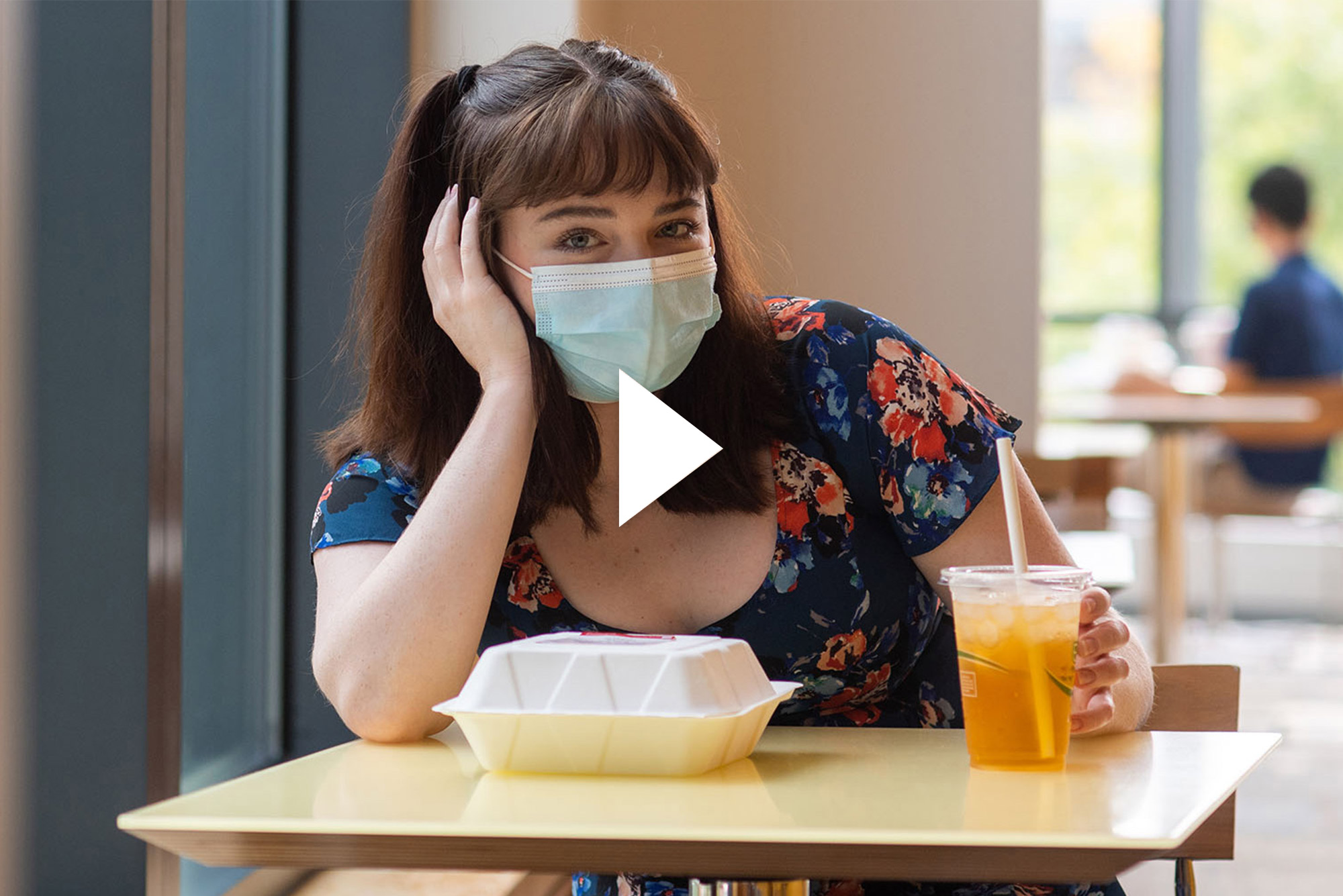 Photo of Brigid Kane (COM'22) sitting at a small dining hall table by herself with a face mask on. A paper to-go container and drink sit in front of her; she rests her hand on her face. Overlay has a video play button.