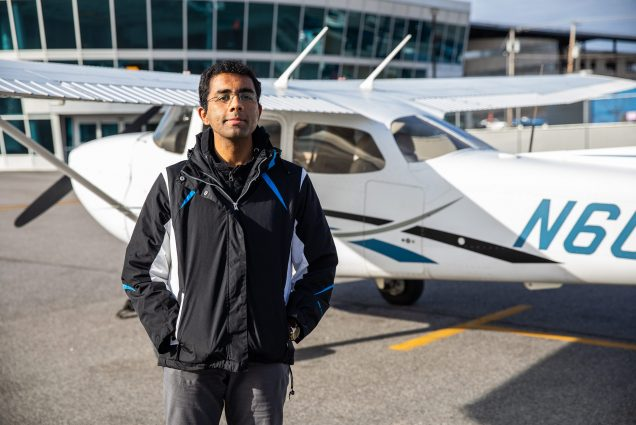 Photo of pilot Dharmesh Tarapore (CAS'18) standing in black jacket in front of a small plane and smiling.