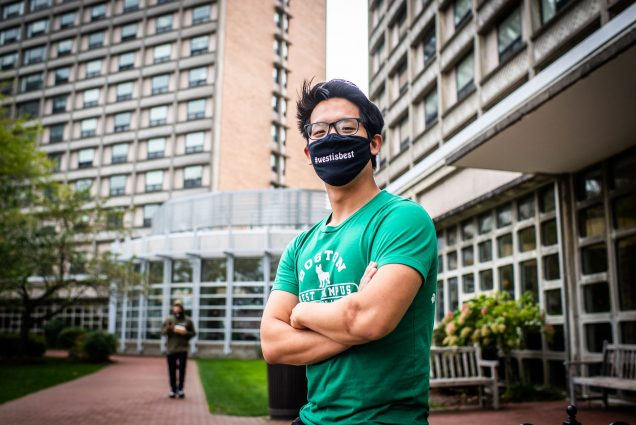 "Photo of Dragon Ding (CAS 21) an RA in Sleeper Hall posing for a photo on West campus on October 5, 2020. Ding wears a black face mask that reads ""West is Best"" and has a green BU shirt on."