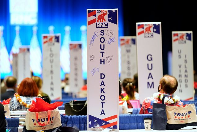 Photo from Monday, Aug. 24, 2020, as delegates watch as the roll call vote of states continues after Vice President Mike Pence spoke at the 2020 Republican National Convention in Charlotte. In the photo, large white posts with RNC branding with state names are seen, such as South Dakota, Guam, and US Virgin Islands. The back of a few people's heads are seen in the background.