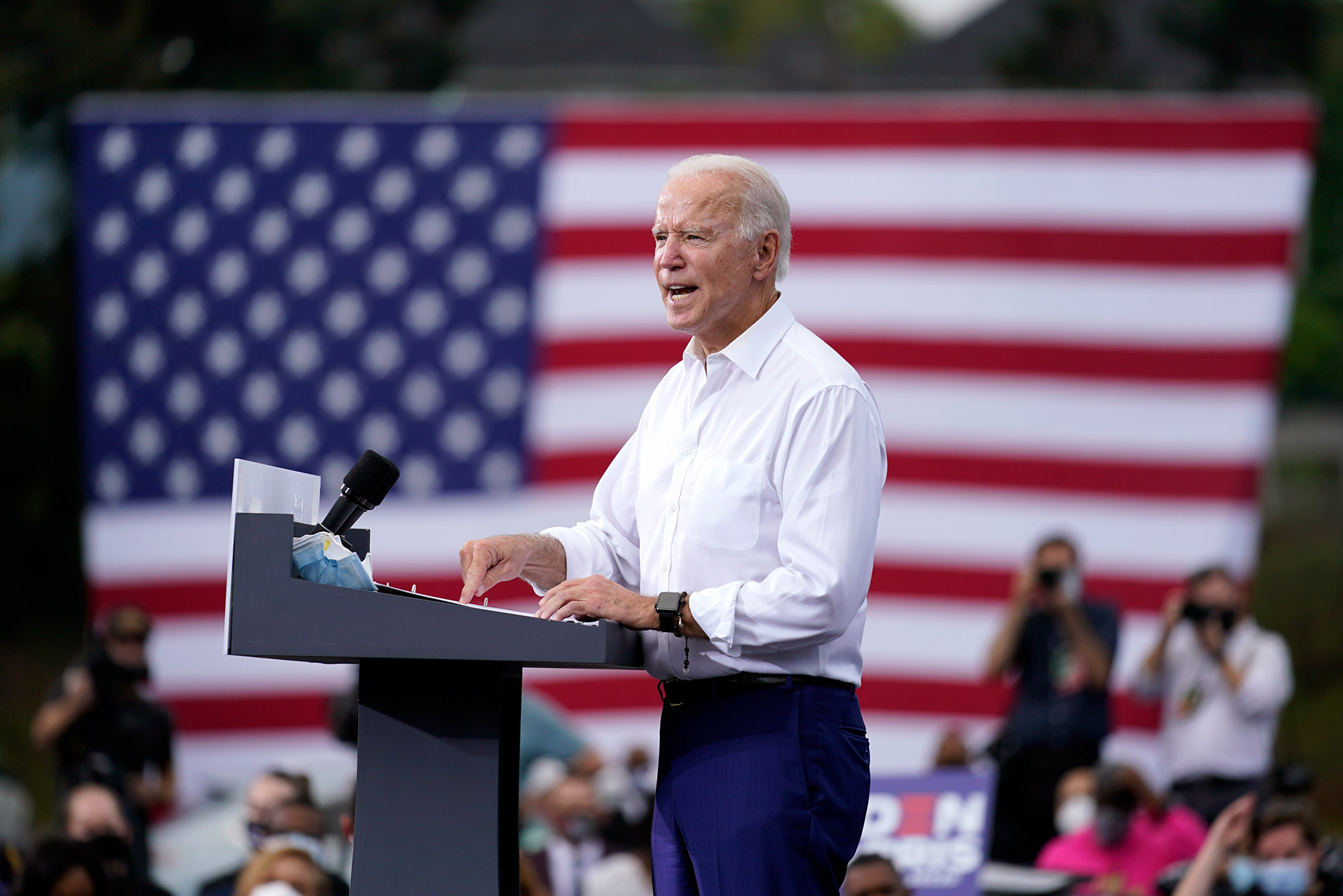 A photograph of Joe Biden giving a campaign speech at a podium with an American flag in the background