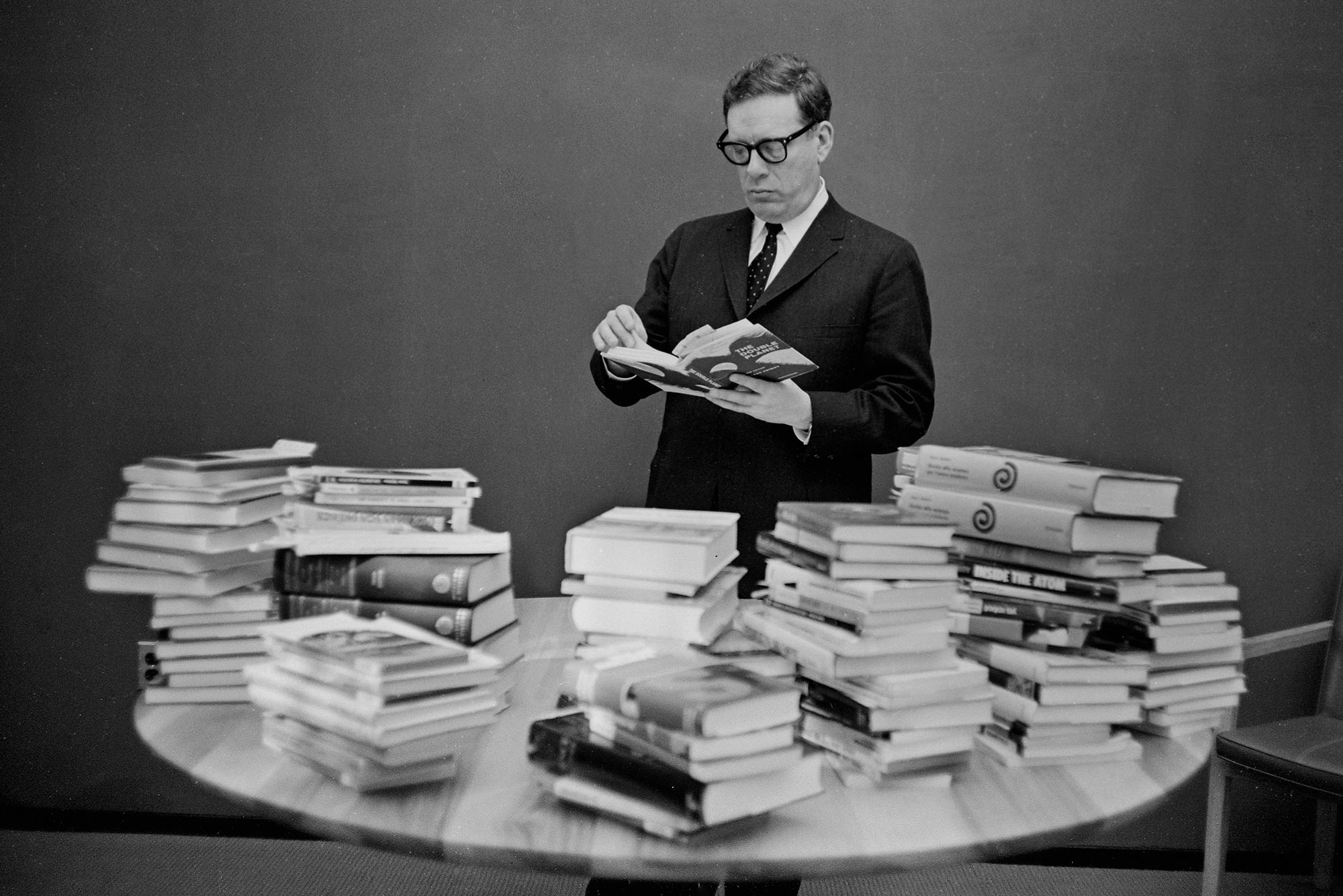 A black and white photo of author Isaac Asimov with 80 books at a Mugar Library event comemmorating the publishing of his 80th book in 1967. The table in front of him is piled high with books; he flips through one, wearing dark thick-rimmed glasses and a suit.