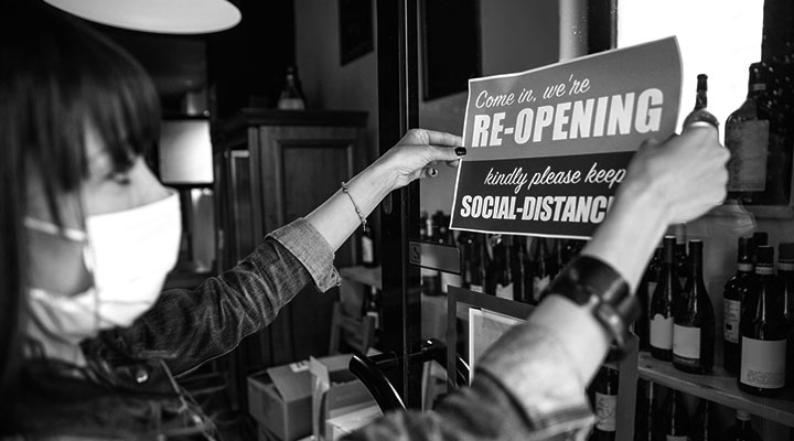 A photo of someone putting a reopening sign on the door of their business