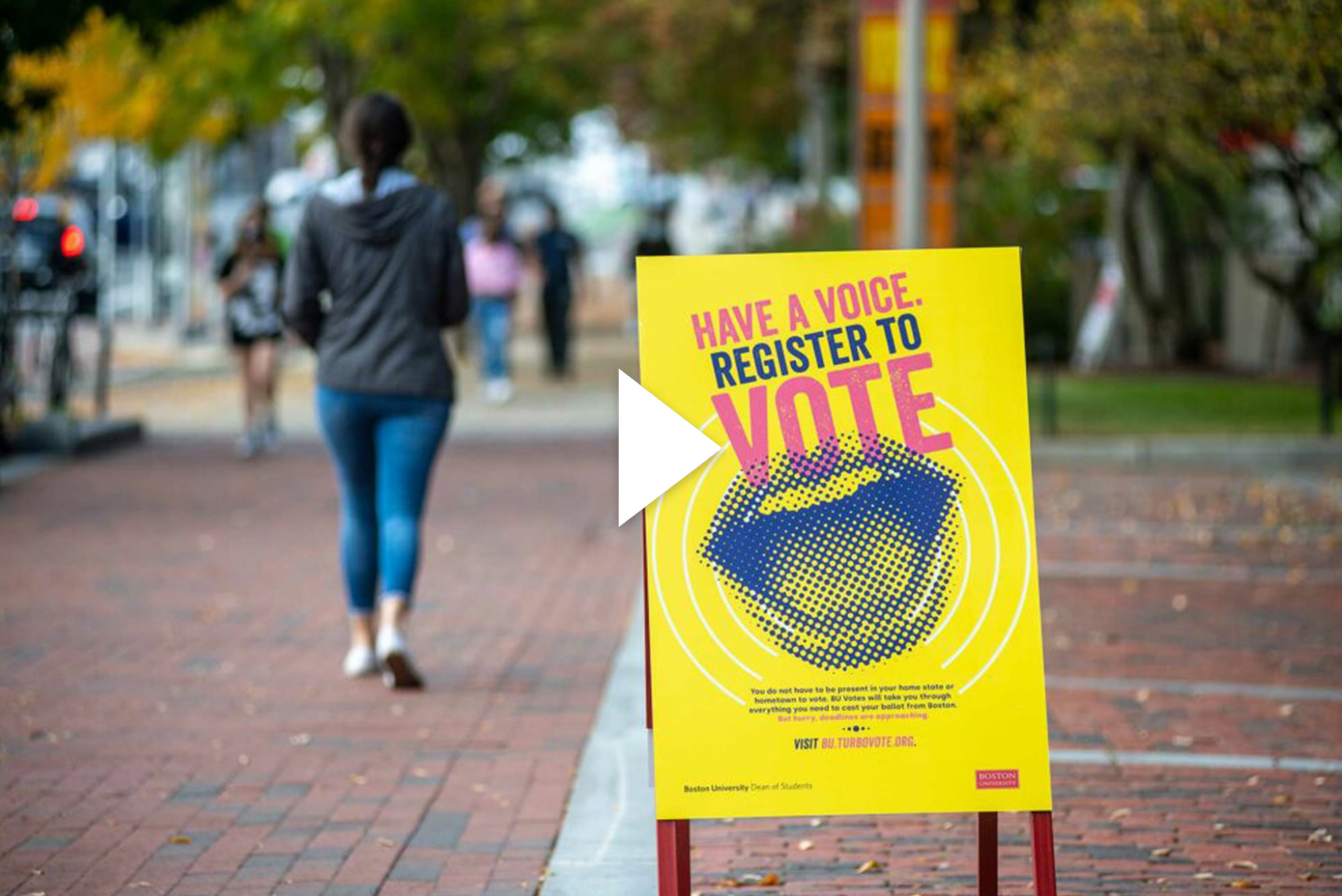 "A sign posted on Commonwealth Ave says ""Have a voice, register to vote"" Overlay has a white video button overlay."